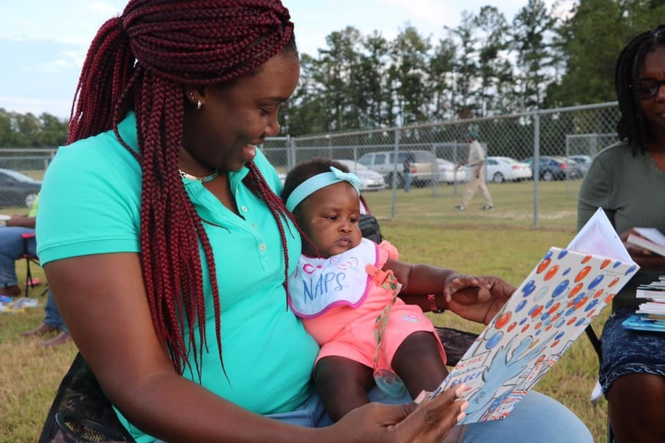 Mom reading to baby at ACS Reading Under the Stars event