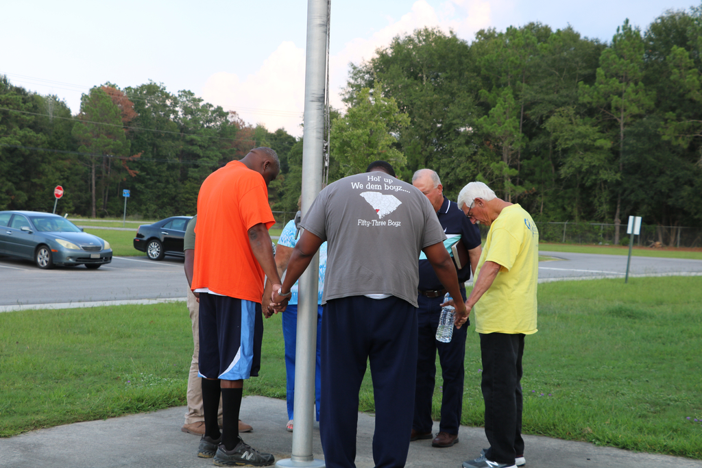 Local community and faith leaders praying at each school.
